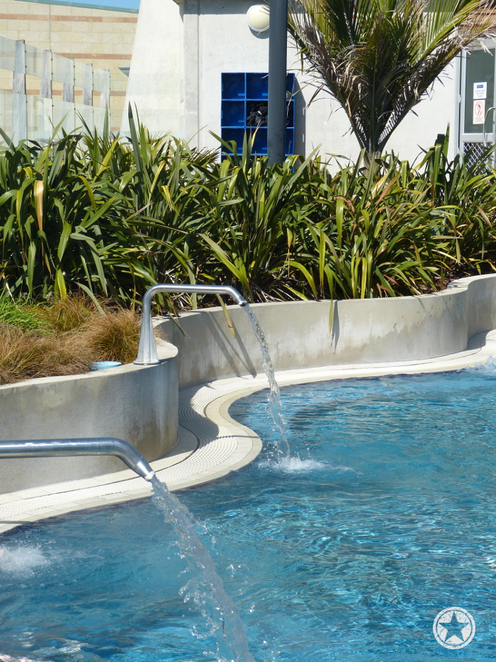 Lounging pool with low pressure water spouts